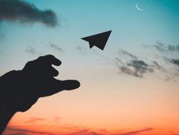paper aeroplane in sunset